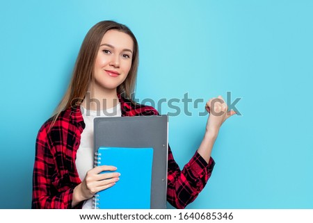 beautiful casual woman holds blue folder and presents to side stock photo © feedough