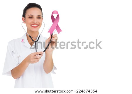 Stock photo: Smiling nurse holding breast cancer awareness pink ribbon with both hands on a pink background