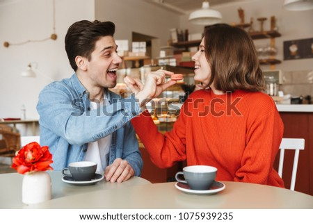 Portrait of adorable couple man and woman dating in cozy bakery, Stock photo © deandrobot
