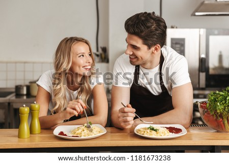 Excited young friends loving couple chefs on the kitchen wipe glasses. Stock photo © deandrobot