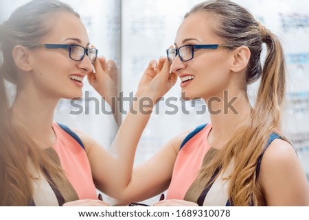 Young woman in optometrists store checking her looks in mirror Stock photo © Kzenon