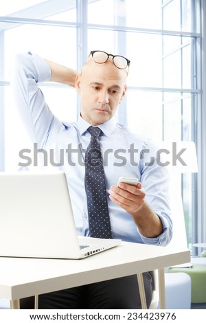 senior businessman using mobile phone in front of office buildin stock photo © boggy