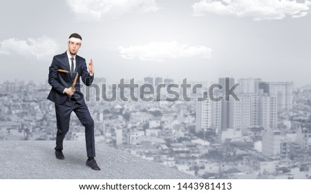 Suited karate man doing karate tricks on the top of a metropolitan city Stock photo © ra2studio