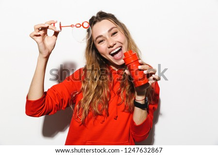 image of adorable woman 20s wearing red sweatshirt blowing soap stock photo © deandrobot
