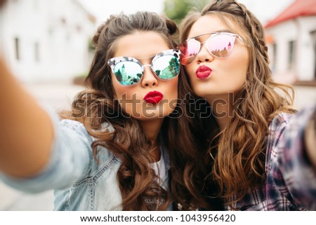 Gorgeous brunette girlfriends with hairstyle, mirrored sunglasses and red lips making selfie with du Stock photo © studiolucky