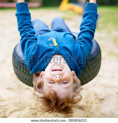 Funny kid boy having fun with chain swing on outdoor playground. child swinging on warm day. Active  Stock photo © galitskaya