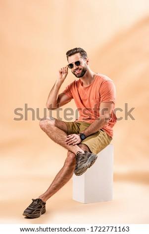 image of european bearded man in white t shirt sitting on grass stock photo © deandrobot