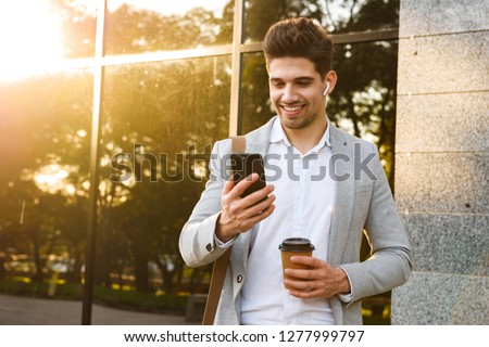 Photo of businesslike men in suits using smartphone while walkin Stock photo © deandrobot