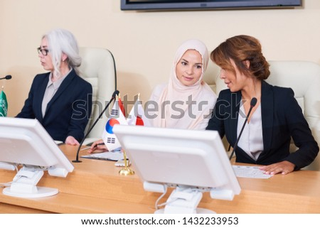 Two young elegant intercultural females consulting about report Stock photo © pressmaster