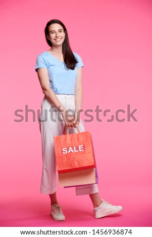 Cheerful female shopper in casualwear carrying bunch of paperbags Stock photo © pressmaster
