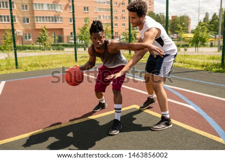 Young basketball instructor helping African sportsman with one of exercises Stock photo © pressmaster