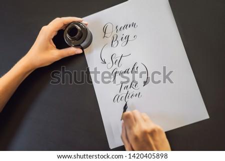 Stock photo: dream big set goals take action. Calligrapher Young Woman writes phrase on white paper. Inscribing o