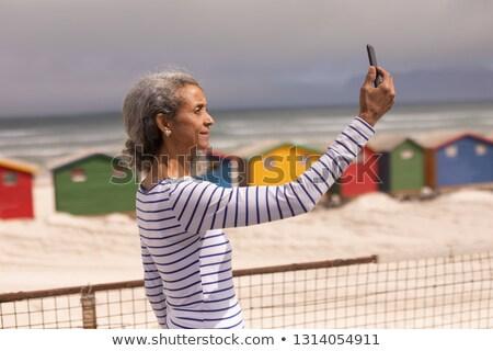 Vista laterale senior donna cellulare passeggiata Foto d'archivio © wavebreak_media