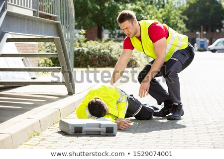 Man Wearing Safety Jacket Looking At Person Falling On Street Stock photo © AndreyPopov
