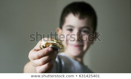 Young boy play with fidget spinner stress relieving toy Stock photo © galitskaya