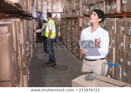 a pretty warehouse team manager checking the inventory stock photo © lopolo