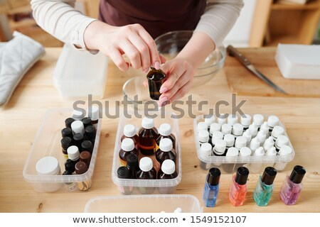Hands of craftswoman opening small bottle with chosen aromatic essence Stock photo © pressmaster