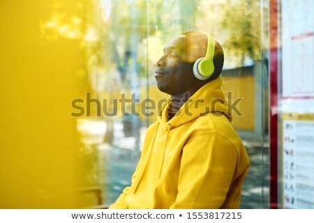 Afryki młody człowiek słuchanie muzyki przystanek autobusowy młodych człowiek Zdjęcia stock © diego_cervo