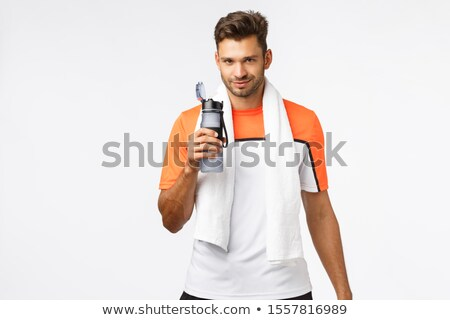 Handsome sportsman with bristle, wear activewear, towel over neck, holding bottle, drink water with  Stock photo © benzoix
