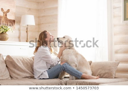 A young woman hugs her beloved pet dog Stock photo © ElenaBatkova