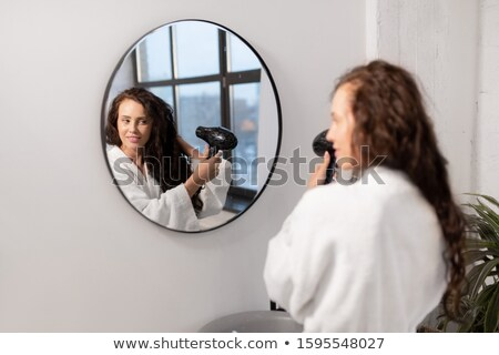 Charming young female with hair-dryer taking care of her dark long wavy hair Stock photo © pressmaster