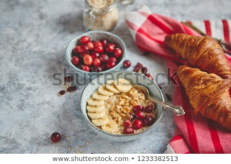 Ceramic bowl of oatmeal porridge with banana, fresh cranberries and walnuts Stock photo © dash