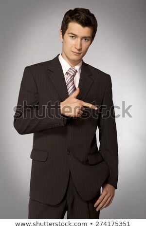 Portrait of aconfident young business man in suit pointing at yo Stock photo © HASLOO