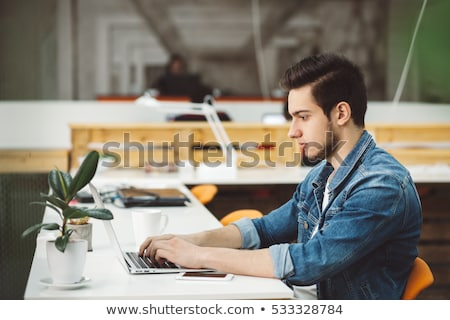 attractive young man working with a laptop at his office he is stock photo © hasloo