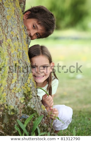 Foto d'archivio: Two Little Children Hiding Behind Tree