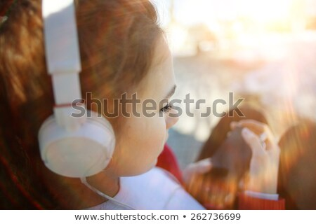 Blonde girl listening to mp3 player Stock photo © Hofmeester