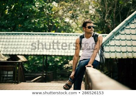 Happy indian man sitting on railing of house Stock photo © ziprashantzi