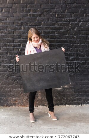 attractive smiling girl in black tight jeans stock photo © acidgrey