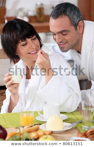 a woman giving a teaspoonful of yoghurt to his husband at breakfast, both are wearing bathrobes Stock photo © photography33