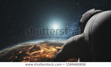 Astronauta guardando terra rendering 3d nero Foto d'archivio © Elenarts