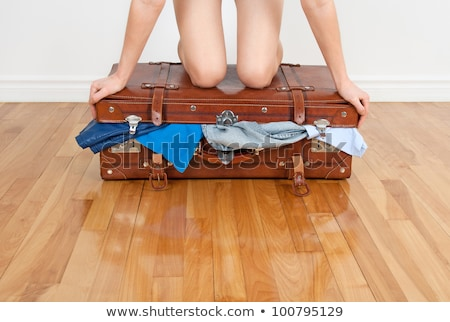 Stock photo: Young fashion travel girl closing full clothes suitcase vacation