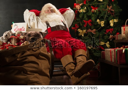 Santa Claus keeping his hands behind head while relaxing at home Stock photo © HASLOO