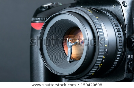 Stock foto: Miniature Man Cleaning Camera Lens