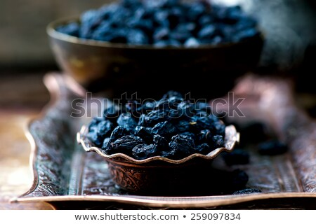 dried dark raisin in oriental metal ware stock photo © zoryanchik
