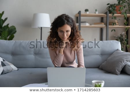 Young woman sitting on sofa and concentrate using the laptop Stock photo © deandrobot