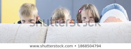 girl peeping out from sofa Stock photo © PetrMalyshev