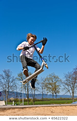 young boy going airborne with a scooter Stock photo © meinzahn