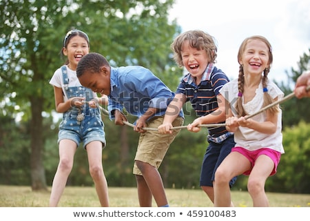 children playing tug of war in the park stock photo © bluering
