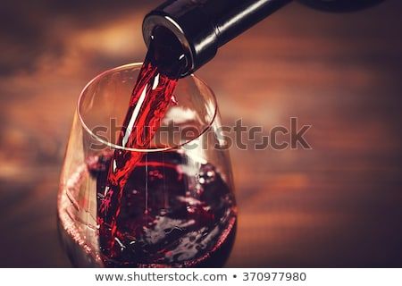 Stock photo: Glass of red wine and a bottle
