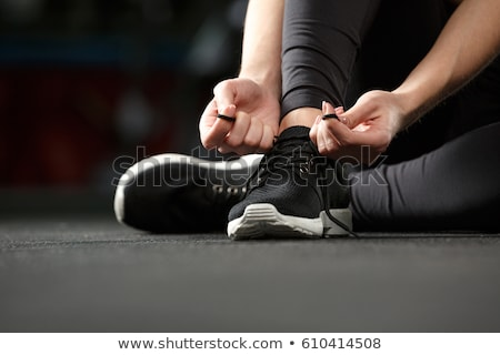 Strong fitness lady sitting and tie laces in gym Stock photo © deandrobot