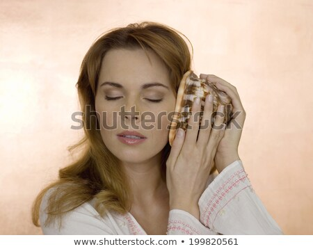 Woman holding shell to ear Stock photo © IS2