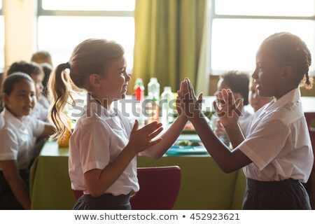 Schoolgirls playing clapping game in canteen Stock photo © wavebreak_media