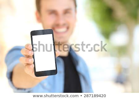 Teenage boy holding up cellular phone and smiling Stock photo © monkey_business