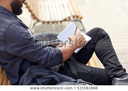close up of man writing to notebook on city street stock photo © dolgachov