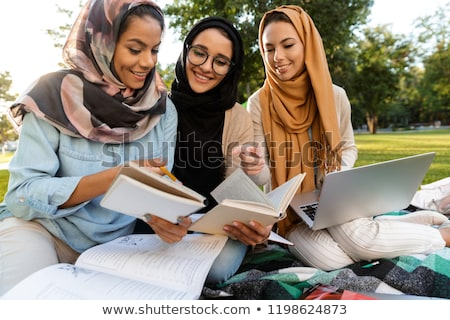 Arabian women students writing in copybooks in park outdoors. Stock photo © deandrobot