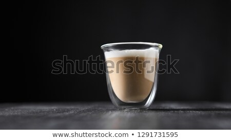 freshly brewed cappuccino with foam in a glass cup on a black wooden table around a dark background stock photo © artjazz